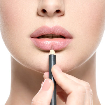 Girl apply lipstick with cosmetic pencil on the lips