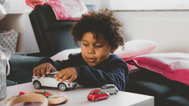 African American kid playing with toy car at home