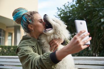 young girl in green coat and multicolored dreadlocks makes a selfie on your smartphone posing with white Samoyed dog in the autumn Park