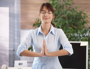Woman meditating in office
