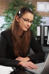 Happy businesswoman working at office desk