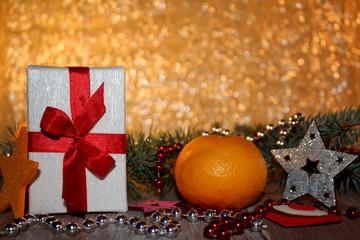 красивый новогодний фон с веточками ели и подарком на блестящем фоне