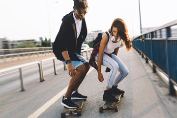 Young attractive couple riding skateboards and having fun