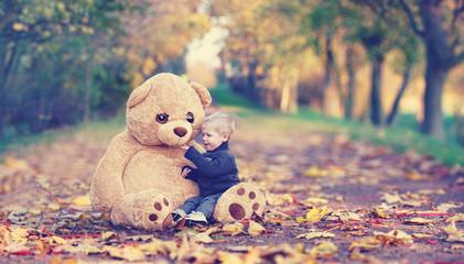 Kind mit seinem Teddy im Park