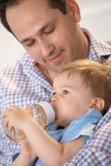 Father feeding baby from bottle