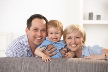 Happy family smiling at camera at home