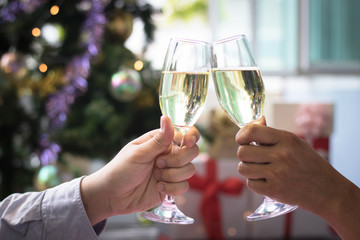 Christmas party drinking concept, glass of champagne with gift box on bokeh background .