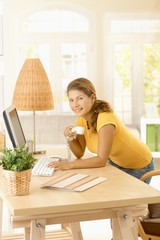 Young woman using computer in home office