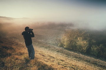 Man is hiking and watching nature with binoculars in the morning.