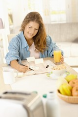 Young woman writing notes in kitchen