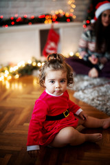 Close up of adorable cute little girl sitting on a floor in Santa clothes in front of her mother for Christmas holidays.