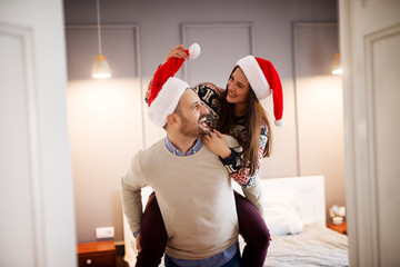 Cute lovely couple with Santa hats and sweaters having a piggyback ride in the bedroom for Christmas holidays.