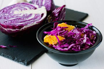 Red cabbage salad with orange in black bowl