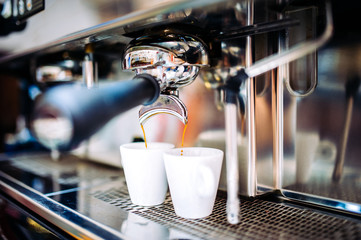 Automatic espresso machine pouring fresh brewed coffee into cups