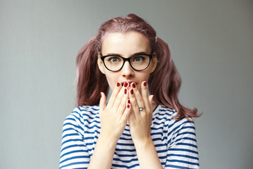 Trendy looking 18 year old girl with pinkish ponytails wearing cat eye glasses and striped t-shirt covering mouth with both hands, having astonished look, shocked with unbelievable information