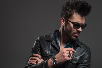 young hipster wearing rings, sunglasses and leather jacket looks down