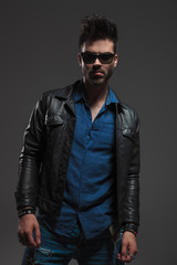 young hipster in leather jacket and sunglasses standing