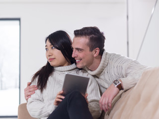 multiethnic couple at home using tablet computers