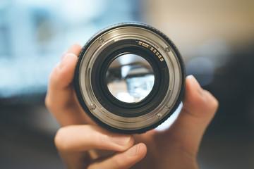 Kamera-Objektiv wird in der Hand gehalten, Nahaufnahme