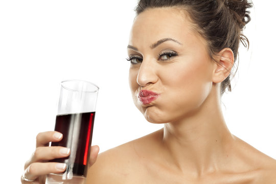 A young woman drinking soda from the glass