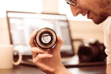 Junger Mann hält Objektiv in der Hand, Laptop im Hintergrund, Vintage-Look