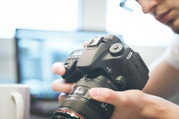 Junger Mann betrachtet Kamera, Laptop im Hintergrund