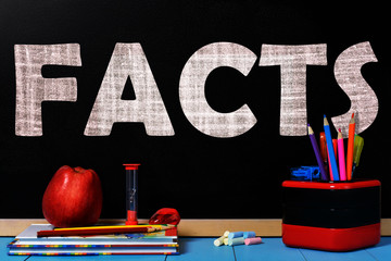 Text facts on black chalkboard with school accessories