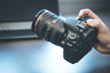 Profi Spiegelreflexkamera in der Hand, Laptop im Hintergrund