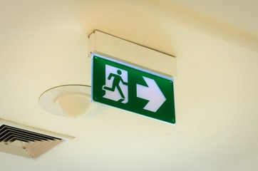 green emergency fire exit sign on ceiling in office building or shopping mall