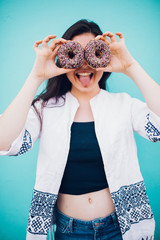 Young woman pulling funny face holding donuts in hands