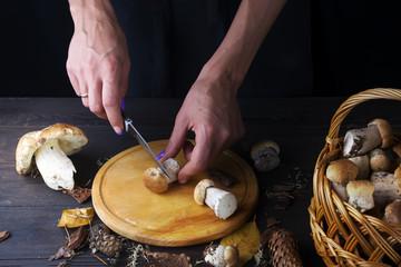 Female hands cut mushrooms not a kitchen board