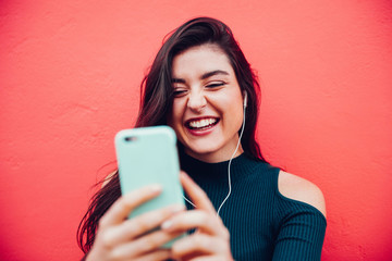 Young happy woman doing video call with smart phone