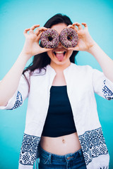 Girl holding chocolate donuts in front of her face