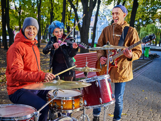 Festival music band. Friends playing on percussion instruments in city park. Fountain and trees in the background. People earn their living on street. Work without a boss.