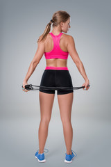 Full length image of a pretty fitness woman doing exercise with skipping rope over gray background