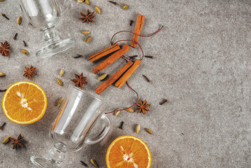 Christmas hot drinks recipes, Set of ingredients for mulled wine: two glass cups, spices, orange. Gray stone background,Top view space