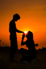 Silhouette of a romantic couple on beauty sunset. Women kneels kissing a boyfriend's hand.