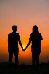 Silhouette of a couple standing and holding hand on sunset.