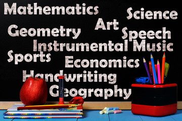 School subjects on black chalkboard with school accessories
