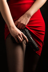 female show stockings under red skirt with gun on black background