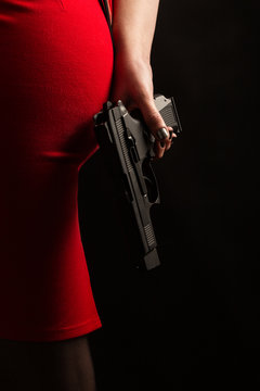 female back in red skirt with gun on black background