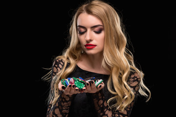 Elegant blonde in a black dress, casino player holding a handful of chips on black background