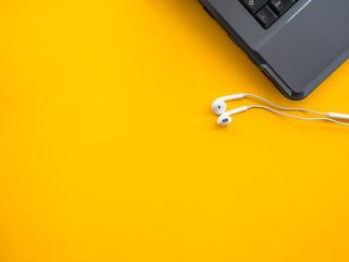 earphones with laptop on yellow background