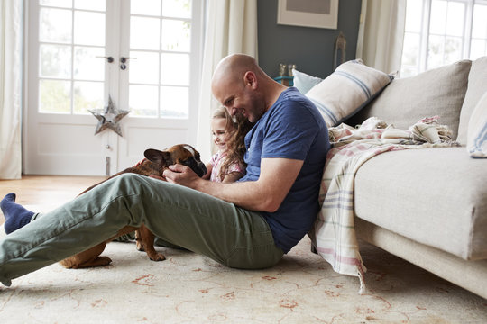 Father and daughter playing with their dog at home