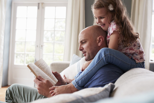 Father reading a book while daughter sitting on his shoulder at home