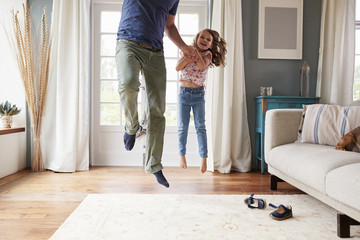 Girl and dad jumping in the air at home holding hands