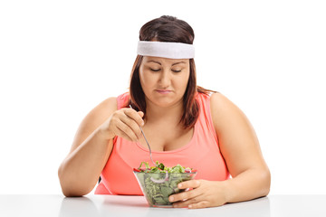Sad overweight woman sitting at a table and looking at a bowl of salad