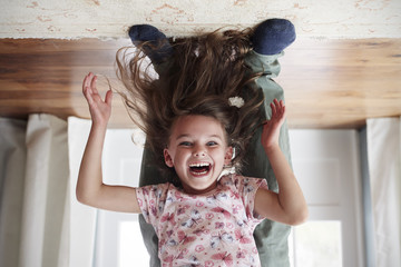 Girl being held upside down by her dad at home, low section