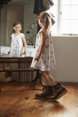 Girl in her dad's boots looking in mirror at home