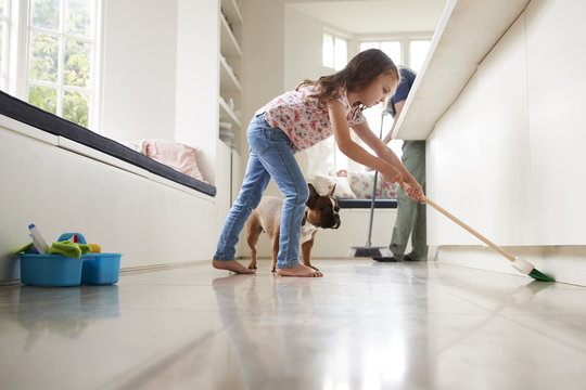 Father and daughter sweeping the kitchen floor together
